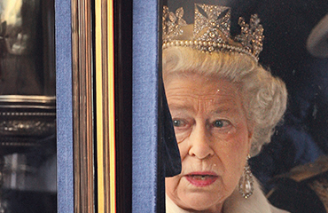 Queen Elizabeth II wearing a crown looking out of the window of her carriage en route to the Palace of Westminster for the state opening of Parliament
