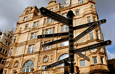 Signposts pointing in different directions in front of a large building