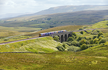 "Settle, United Kingdom - July 30, 2011: A Northern Rail DMU service from Leeds to Carlisle (Route 7) crossing the picturesque Lunds stone viaduct near Garsdale Station on the famous Settle and Carlisle railway line in the Yorkshire Dales. Northern Rail or ""Northern"" is a rail franchise owned by Serco-Abellio."