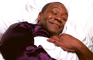 Lenny Henry sleeping in bed cuddling pillow
