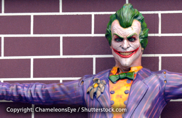 The Joker, villain from the Batman comics, stands in front of a brick wall